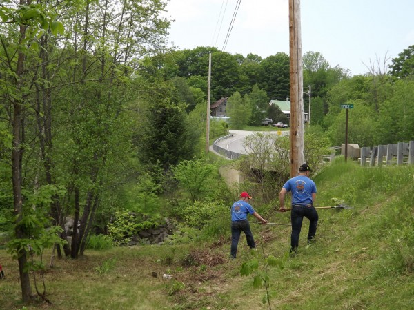 Two members of the Western Maine Young Marines clear grass off the side of a hill on Route 154 in front of what will be renamed the Remember Me Bridge in Harmony on Saturday, May 26, 2012. The area to the left will be made into a memorial area to remember those who affected by domestic violence. The bridge, along with another bridge on Route 150 in Harmony that will be renamed the Amy-Cote-Monica Bridge, in honor of Amy Lake and her two children who were killed by her husband, Steven Lake, will be dedicated on June 2.