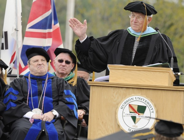 Old Town native and Husson alumnus Arthur A. Comstock, flanked by university president Robert Clark (left), gestures to graduates at the 113th Commencement of Husson University in Bangor on Saturday, May 5, 2012. Comstock, who graduated from Husson College in 1956, was given an honorary doctoral degree in business administration.