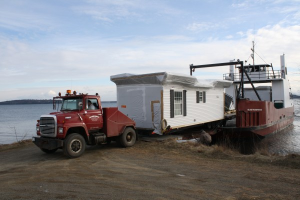 One of the new affordable housing units, a modular home, is delivered by barge to Islesboro.