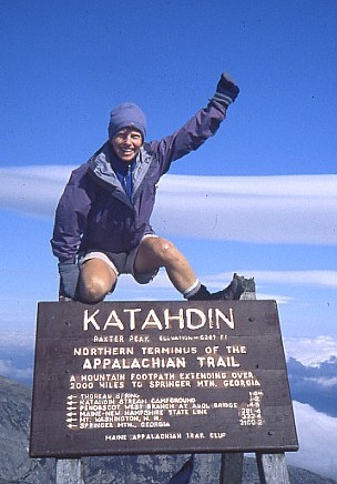 Sandy Sabaka summits Mount Katahdin, finishing her thru-hike of the Appalachian Trail on Oct. 13, 2002. She celebrates at the summit sign on Baxter Peak.