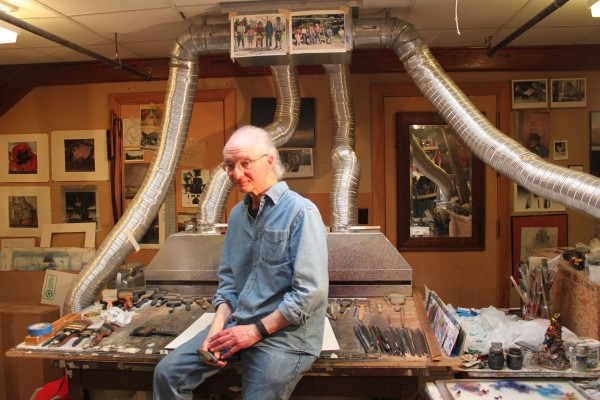 Landscape painter Michael Lewis sits for a photo in his studio in the attic of Fernald Hall at the University of Maine on May 7, 2012. The extensive ventilation system behind Lewis is necessary because he works with oil paint diluted with turpentine, an organic solvent with health risks.