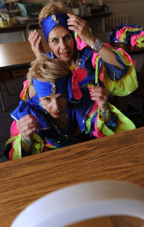 Bunny Gibson (top) and Judy Commeau check their head pieces in a mirror during a quick change of costumes at a dress rehearsal of &quotThe Skylight Club&quot at the Hammond Street Senior Center in Bangor on Thursday, May 17, 2012.
