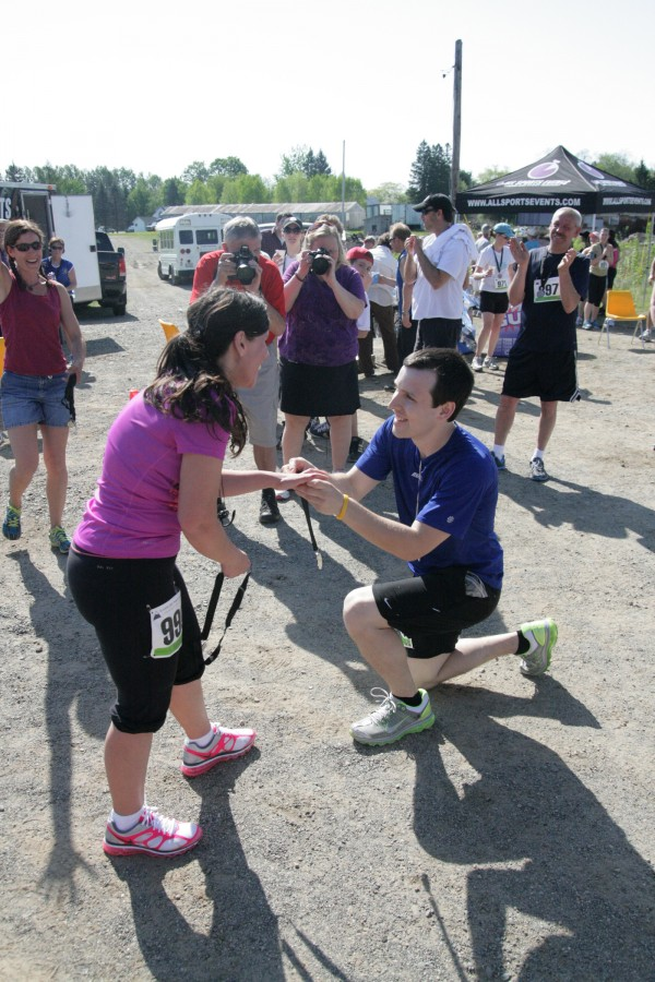 Michael Glynn (kneeling) places an engagement ring on the finger of his new fiancee, Mary Graziano, moments after they completed the Sugarloaf 15K in Kingfield. The Bangor couple work as teachers at the Hartland Consolidated School.