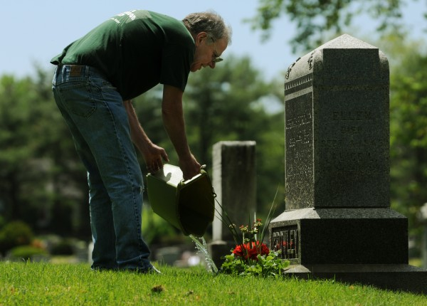 Terry Milan of Bangor waters flowers he planted on the grave of his great-grandfather in Mt. Pleasant Cemetery on Sunday, May 27, 2012. Milan was tending numerous graves in the cemetery Sunday.