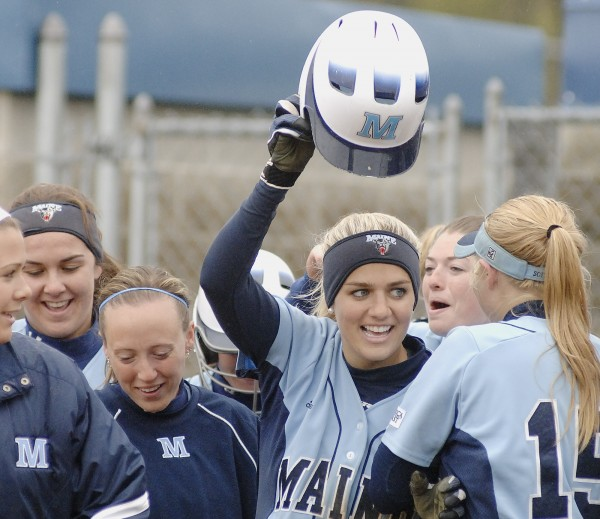 UMaine softball player Margaret Hilton waves her helmet as she celebrates with teamates her two-run home run in the second inning of their game with Boston University in Orono Tuesday, May 1, 2012.