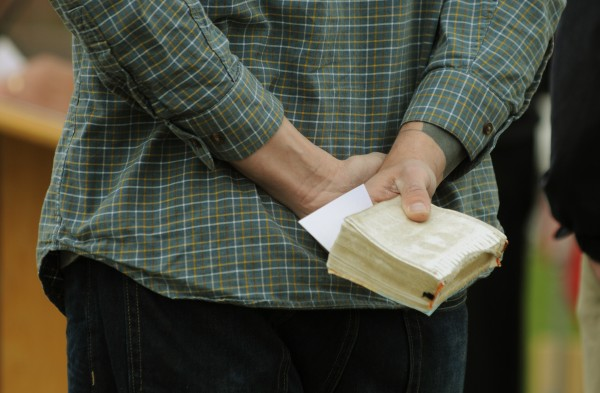 A coverless bible is held by a member of the clergy as prayers were offered to city officials, schools, armies and members of the fire department along the Bangor Waterfront on Thursday, May 3, 2012 as part of National Prayer Day.