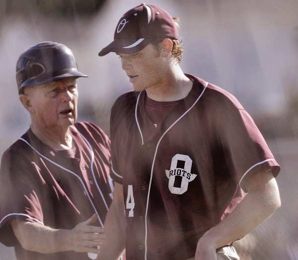 Orono High School baseball pitcher Tyler Eddy (14) gets congratulated by assistant coach Wally Covell after the home half of the fourth inning of their game against Old Town High School in Old Town Thursday, May 24, 2012.
