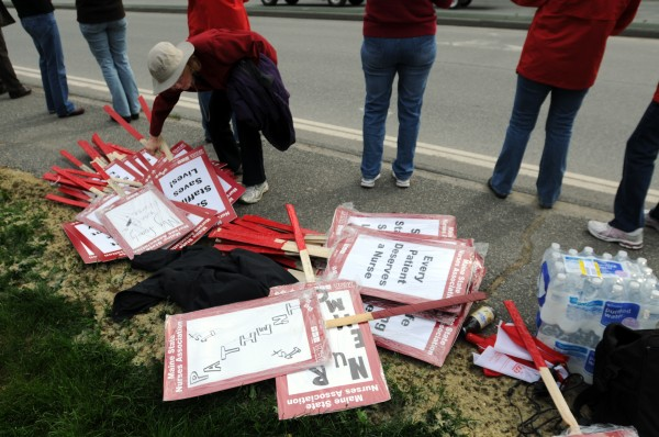 A women selects a sign from a pile to support Members of the Maine State Nurses Association as they rally in front of EMMC in Bangor on Tuesday, May 15, 2012, for an informational picket to allow members of the public to know about their negotiations with EMMC administrators.