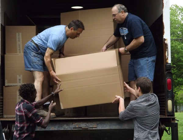 Sammy Gachagua (bottom left) and Jordan Valente (bottom right) help load a box of shoes onto a C.M. Almy truck at Maine Central Institute in Pittsfield on Thursday, May 24, 2012. Gachagua has helped collect more than 3,000 pairs of shoes that will be donated to an orphanage and surrounding communities in his native Kenya.