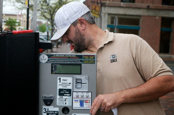 Dan Culliton of Cale America installs a new solar-powered parking meter on Commercial Street in Portland that accepts credit cards Monday morning May 14, 2012.
