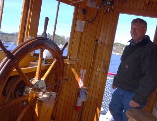 Steve Pagels, owner of the Prudence, poses in the wheelhouse of the Maine-built vessel. Built in 1911 as a steam-powered ferry, it will offer passenger excursions out of Bangor and Belfast this summer.
