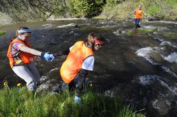 Gracie Brochu (right), 15, helps fellow volunteer Ellie Leighton, 15, as they comb the bank of the Sedgeunkedunk Stream for trash with fellow Brewer High School freshman classmate Jordan Burgess (background) during the eighth annual riverside cleanup in Brewer Saturday morning, May 12, 2012. Over the years, scores of local volunteers have removed tons of garbage and debris in areas along the Penobscot River.
