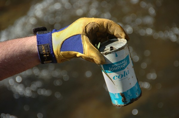 Deputy Brewer Mayor Kevin O'Connell holds up an old discarded Howard Johnson's cola can, one of many trash items he and others removed from an area along the Sedgeunkedunk Stream in Brewer Saturday morning, May 12, 2012.