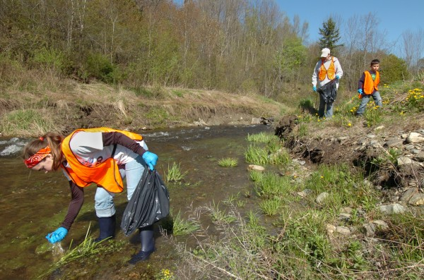 Ellie Leighton, 15, of Brewer removes a ceramic shard from the the Sedgeunkedunk Stream as James Bertolino, 6, and his mom, Janet Bertolino of Brewer, comb the bank for trash during their volunteer cleanup efforts in Brewer Saturday morning, May 12, 2012.