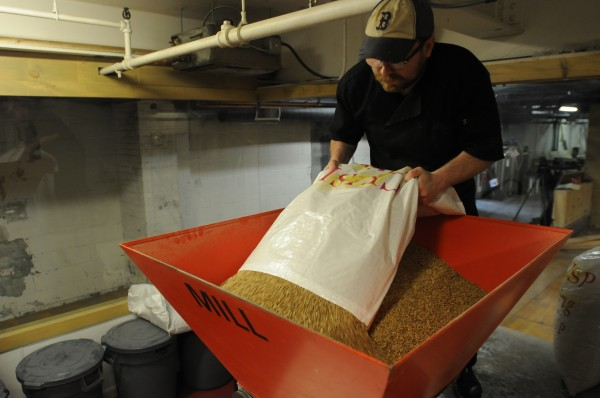 Assistant brewer Michael Carey pours grain into a mill at Sea Dog Brewing Co. in Bangor on Tuesday, May 1, 2012. The Sea Dog is opening a new beer tasting room in the basement and is expanding its beer making capacity.