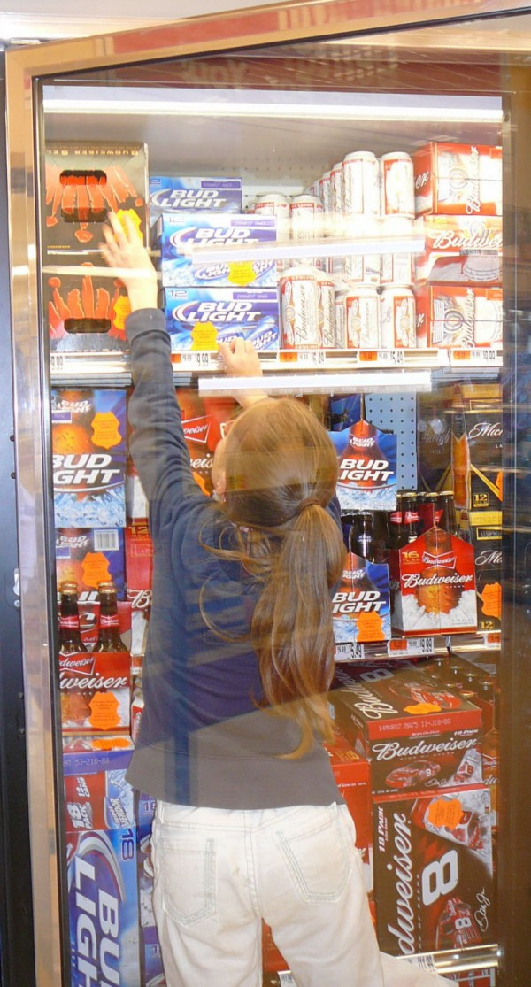 In this file photo from 2007, a student from Warsaw Middle School puts stickers on beer at Bud's Shop 'n Save in Pittsfield to raise awareness about providing alcohol to minors.