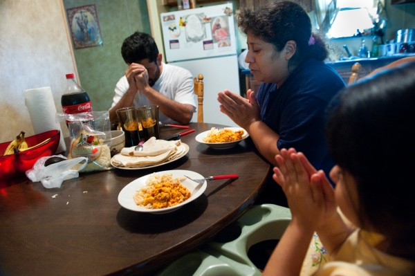 From left to right, Armando Macias, 43, Nora Terrazas, 34, and Lesly Macias, 3, pray before eating lunch in their trailer home. Amid a crackdown on immigrants, the family has stayed in Albertville, Ala., but does not feel welcome.