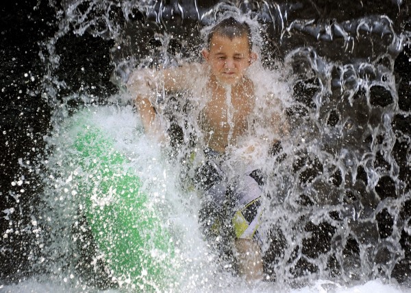 James Linderman catches water from the spillway at Buck Creek Park to cool off from record heat in Helena, Ala., on Friday, June 29, 2012.