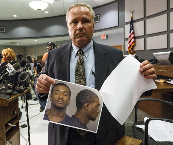 Auburn Police Chief Tommy Dawson holds up head shots of suspect Desmonte Leonard, 22, of Montgomery, Ala., during a news conference, Sunday, June 10, 2012, in Auburn, Ala. Police say Leonard has been charged with capital murder and has not yet been captured, in connection with a shooting at an apartment complex near Auburn University that left three dead and three others injured. Dawson urged Leonard to turn himself in and also said authorities were searching for two other persons of interest.