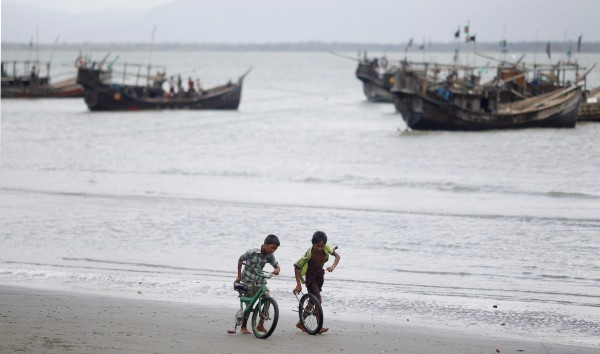 Children play with a broken bicycle on the bank of Naf river at Shahporir Dwip in Taknaf, Bangladesh on Tuesday, June 19, 2012. Bangladesh refused to allow Rohingya Muslim refugees fleeing sectarian violence in Myanmar despite call by the United Nations.