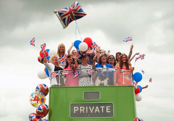 Racegoers cheer on an open-top bus during Investec Ladies' Day of the Investec Derby Festival at Epsom Racecourse in Epson, southern England on Friday, June 1, 2012. Queen Elizabeth II kicks off a long weekend of celebrations of her 60-year reign by going to the races.