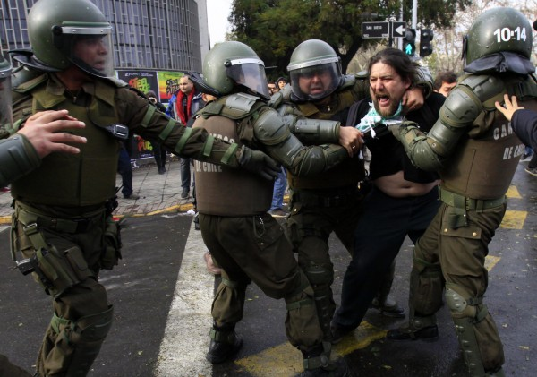 A man is carried away by riot police during a demonstration protesting the premiere of a documentary about the late Gen. Augusto Pinochet in Santiago, Chile, Sunday June 10, 2012.  Police used tear gas and water cannons to try to disperse hundreds of anti-Pinochet demonstrators against the documentary about the run-up to his dictatorship years and casting him as a national hero who saved Chile from communism.