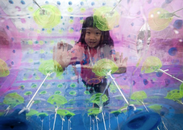 A child plays inside a balloon float on water at the Chaoyang Park during International Children's Day in Beijing on Friday, June 1, 2012.