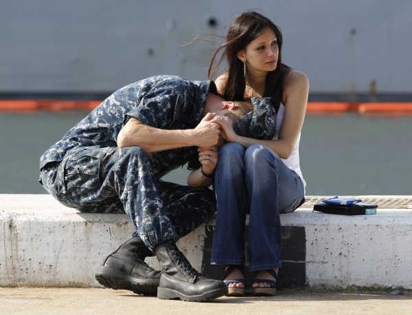 U.S. Navy Gunners Mate, Steven Joyce, puts his head in the lap of his wife, Damara, as he says good bye as his ship the USS Carr prepares to depart Naval Station Norfolk en route to the Persian Gulf in Norfolk, Va., on Friday, June 1, 2012.  The ship is part of the group leaving with the floating special operations base ship USS Ponce for deployment to the Persian Gulf.