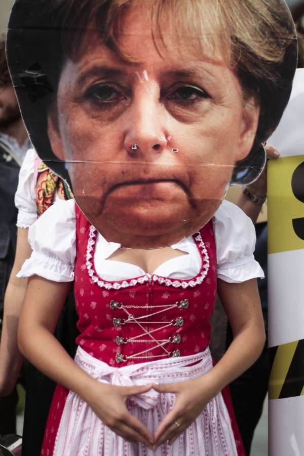 A woman dressed with a Bavarian dirndl and a huge Angela Merkel mask takes part in a protest against a planned controversial benefit program for child care near the chancellery in Berlin, Germany, Wednesday, June 6, 2012.