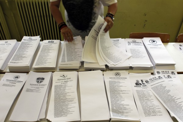 A woman arranges ballot papers at a polling station in Athens, on Sunday, June 17 2012. Greeks voted Sunday for the second time in six weeks in what was arguably their country's most critical election in 40 years, with the country's treasured place within the European Union's joint currency in the balance.