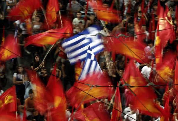 Supporters of the Greek Communist party wave flags during the main pre-election campaign in central Athens on Friday, June 15, 2012. Greeks cast their ballots this Sunday for the second time in six weeks, after May 6 elections left no party with enough seats in Parliament to form a government and coalition talks collapsed.