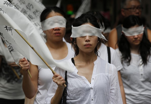 Protesters wear white dresses and cover eyes with white clothes to show their own expression to mourn for the death of Chinese labor activist Li Wangyang during a protest march in Hong Kong, Sunday, June 10, 2012. Li, imprisoned for two decades, died in a hospital Wednesday one year after being released from jail, and a relative raised doubt on the official explanation that he had hanged himself. The activist had advocated for independent labor unions in central China's Hunan province and was caught in the sweeping nationwide crackdown on all forms of dissent after the Tiananmen Square democracy protests were quashed in 1989.
