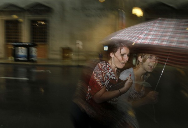 Pedestrians seek shelter under an umbrella as a thunderstorm moves quickly through the Chicago area Friday, June 29, 2012. Most of Illinois is in at least a moderate drought after weeks with little rain.