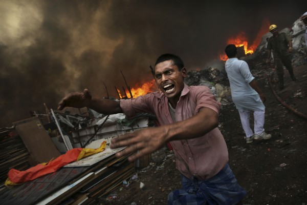 An Indian shouts for water as a shanty town is engulfed in flames in New Delhi, India on Friday, June 22, 2012. A fire swept through a slum in the Indian capital on Friday, destroying hundreds of shanties where residents had collected scrap plastic and rubber for resale. No one was reported injured or killed, fire department chief A.K. Sharma said.