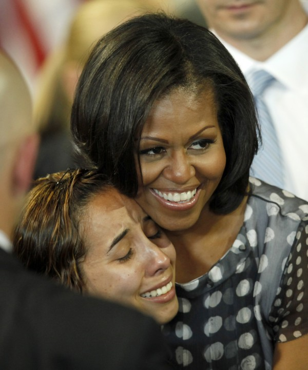 First lady Michelle Obama hugs a woman in the audience after Illinois Gov. Pat Quinn signed into law a measure allowing military personnel and their spouses a quicker transfer of their professional licenses to Illinois during a military relocation, Tuesday, June 26, 2012, in Chicago. Illinois becomes the 23rd state to enact such legislation.