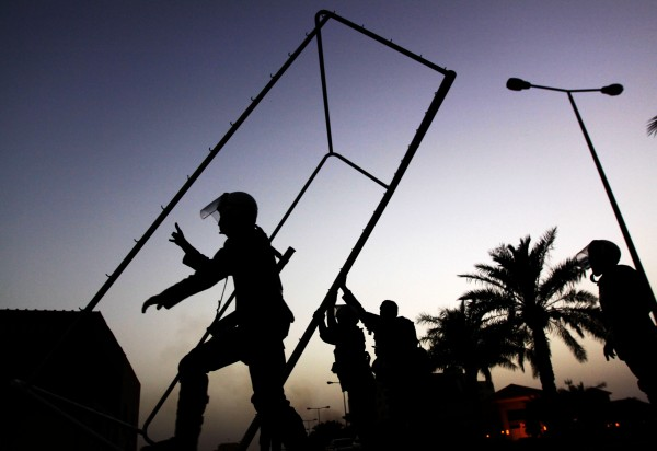 Riot police clear a soccer goal and other debris used as roadblocks by Bahraini anti-government protesters, unseen, to slow the police pursuing them during clashes Friday, June 8, 2012, in Abu Saiba, Bahrain. Riot police in Bahrain fired tear gas and stun grenades Friday as tens of thousands of protesters staged the biggest anti-government demonstrations in weeks in the divided Gulf nation.