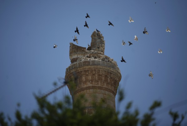 Birds fly over a destroyed minaret of a mosque at the northern town of Ariha, on the outskirts of Idlib, Syria, Sunday, June 10, 2012. The U.N. said several weeks ago that thousands of people have been killed since the uprising began in March last year.