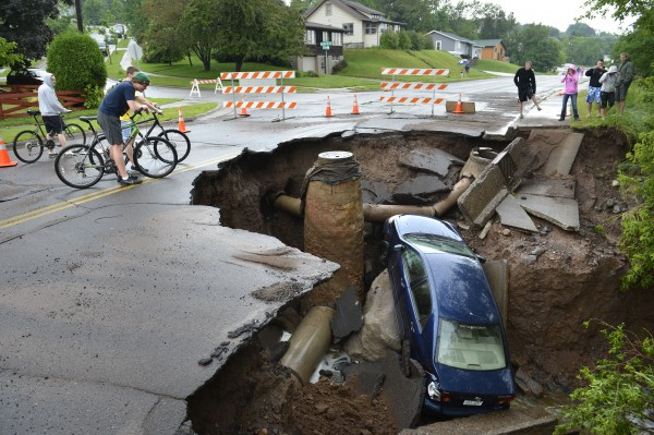 A car sits in a giant sinkhole in Duluth, Minn. Wednesday, June 19, 2011. Residents evacuated their homes and animals escaped from pens at a zoo as floods fed by a steady torrential downpour struck northeastern Minnesota, inundating the city of Duluth, officials said Wednesday.