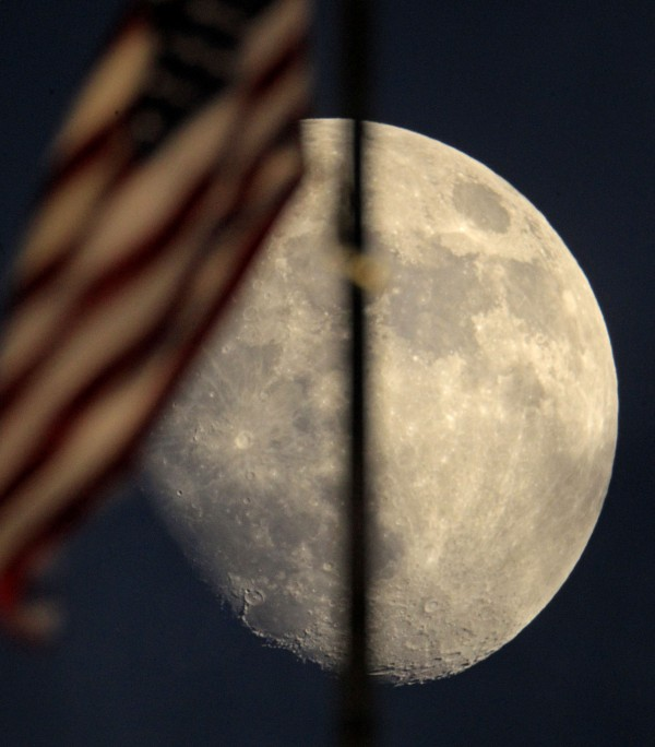 An American flag atop city hall waves in the wind against the backdrop of a waxing moon Thursday, May 31, 2012, in Kansas City, Mo.