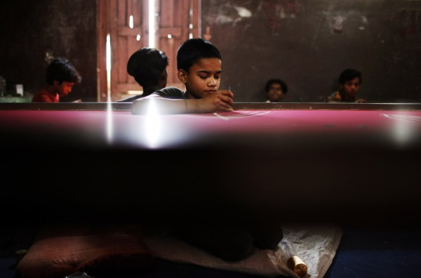 An Indian migrant boy works in a sari factory on World Day Against Child Labor in Katmandu, Nepal on Tuesday, June 12, 2012. This day serves as a catalyst for the growing worldwide movement against child labor.