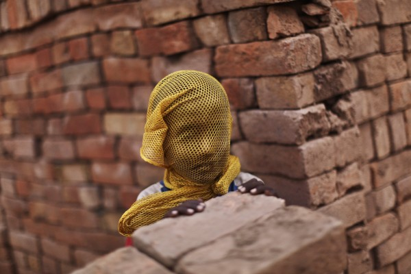 A Pakistani boy who lives near by a brick factory, covers his face with a scarf to avoid a sand storm, on the outskirts of Islamabad, Pakistan, Wednesday, June 6, 2012.