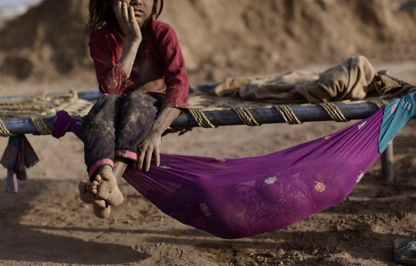 Pakistani Naginah Sadiq, 5, who works in a brick factory, rests on a bed next to her sister Shahzadi, 8 months, sleeping in a hammock attached to the bed, on World Day Against Child Labor, on the outskirts of Islamabad, Pakistan on Tuesday, June 12, 2012. The World Day Against Child Labor is observed on June 12 across the world including Pakistan to raise awareness and contribute to end child labor. Naginah earns 250 Rupees ($2 .77) per day according to her father.