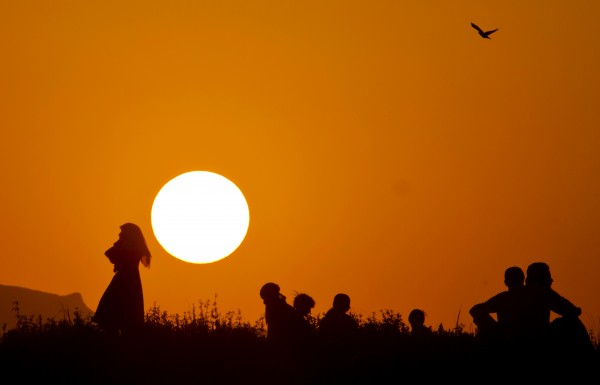 Afghan refugee youth are silhouetted against the sunset as they gather at a slum on World Refugee Day on the outskirts of Islamabad, Pakistan on Wednesday, June 20, 2012. World Refugee Day, a day initiated by the United Nations to raise awareness on the plight of refugees worldwide, is observed on June 20 every year.