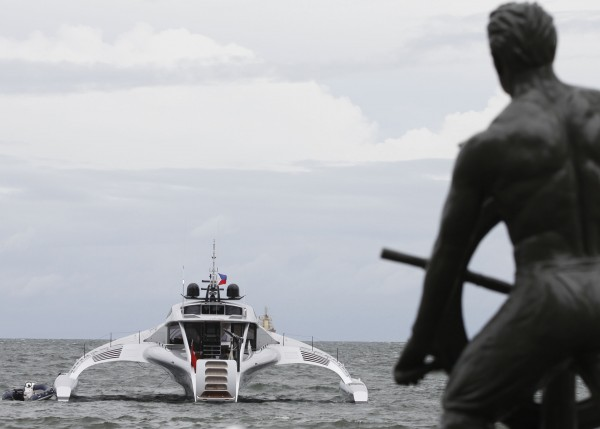 A statue of a sailor is seen on the foreground as the $15 million futuristic yacht Adastra launched in China this year for a Hong Kong billionaire is docked in Manila Harbor, Philippines on Friday, June 29, 2012. The 140-foot-long elongated luxury yacht, made of carbon fiber and kevlar to make it extra light, was designed by Australian boat builder McConaghy for Hong Kong shipping magnate Anthony Marder.