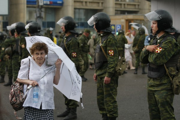 An elderly woman holds a white umbrella as a symbol of protest, as she walks past a line of police officers after a massive opposition rally in central Moscow, Russia on Tuesday, June 12, 2012. Tens of thousands of Russians flooded Moscow's tree-lined boulevards Tuesday in the first massive protest against President Vladimir Putin's rule since his inauguration, as investigators sought to raise the heat on the opposition by summoning some of its leaders for questioning just an hour before the march.