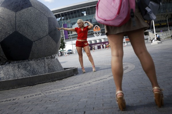 A woman poses for her friend in front of the Donetsk stadium during the Euro 2012 soccer championship in Donetsk, Ukraine, Friday, June 8, 2012.
