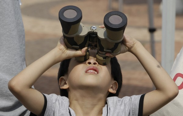 A young boy uses a pair of binoculars with special filters, to observe the transit of Venus at the National Science Museum in Gwacheon, south of Seoul, South Korea, Wednesday, June 6, 2012. From the U.S. to South Korea, people turned their attention to the daytime sky on Tuesday and early Wednesday in Asia to make sure they caught the rare sight of the transit of Venus. The next one won't be for another 105 years.