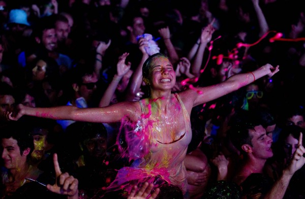 A reveler reacts during a glow paint party in the early hours on Saturday, June 23, 2012. Around a thousand youths danced to techno music while spraying each other with paint, while the organizers sprayed the party goers from the stage.
