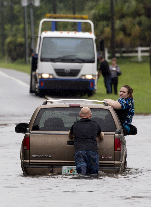 A motorist pushes his car through deep flood water near Live Oak Fla., Tuesday, June 26, 2012. Flood water from Tropical Storm Debby continues to pound Florida as it slowly churns northward through the Gulf.