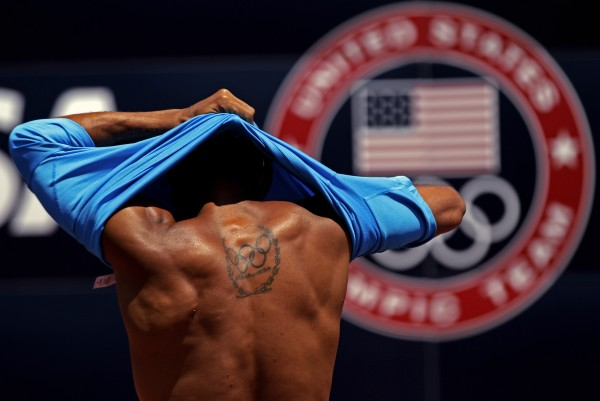 Bryan Clay of Austin, Tex., takes off his shirt as he warms up before the U.S. Olympic Track and Field Trials Wednesday, June 20, 2012, in Eugene, Ore. Clay, the current Olympic champion in the decathlon, is scheduled to compete.